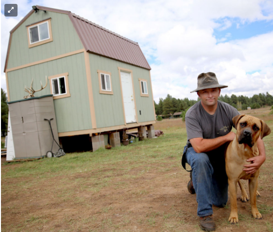 Collin Bass and his dog Lucca in front of their tiny house in Flagstaff, AZ.